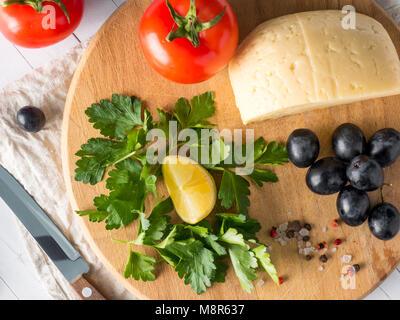 Pezzo di formaggio con prezzemolo, pomodori uve su un tagliere con un coltello. Foto Stock