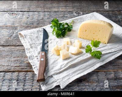 Pezzo di formaggio con il prezzemolo una biancheria in legno rustico sfondo. Foto Stock