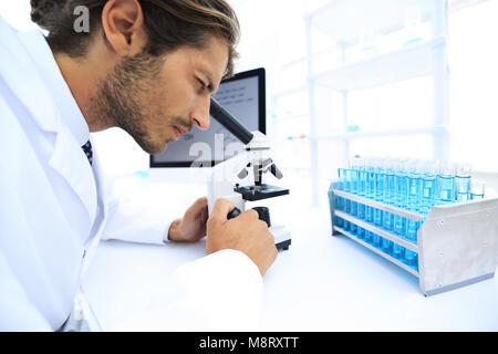 Giovani laboratorio di uno scienziato guardando al microscopio in laboratorio Foto Stock