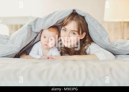 Ritratto madre gioca con i bambini sul letto. Foto Stock
