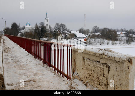 Vista su un villaggio con una chiesa coperta di neve e di un ponte su un piccolo fiume costruito per commemorare il cinquantesimo anniversario dell'URSS, Porechye village, Ner