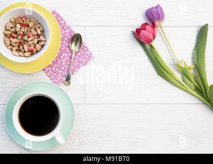 Guardando verso il basso a partire da sopra su un bianco, tavolo in legno top con una colazione femminile di muesli e caffè lungo con i tulipani, fiori e copia di spazio. Foto Stock