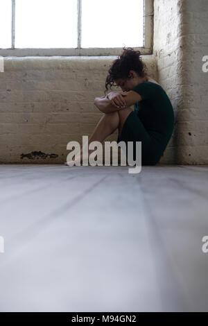 Vista laterale di un triste giovane donna che indossa un abito sabato sul pavimento mediante la finestra Foto Stock