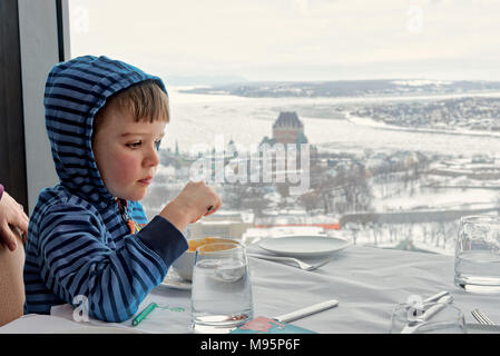 Un bambino di cinque anni, ragazzo di mangiare in Ciel! Il ristorante rotante in Quebec City, con lo Chateau Frontenac e congelata di St Lawrence al di là.