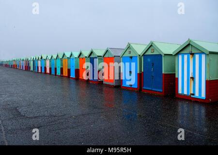 Una linea di 40 cabine sulla spiaggia, con diverse porte multicolore su un calcestruzzo lungomare, la spiaggia più vicina capanne sulla destra dell'immagine sono grandi andando t Foto Stock
