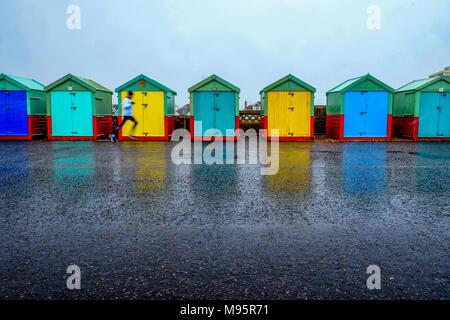 Brighton Seafront sette cabine mare, cinque con il blu e il verde di porte e due con sportelli gialli spiaggia capanne sono in linea su un calcestruzzo promenade il Foto Stock