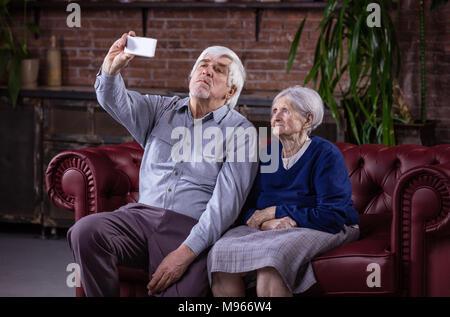 Coppia senior tenendo selfie con smart phone comodamente seduti sul divano di casa Foto Stock