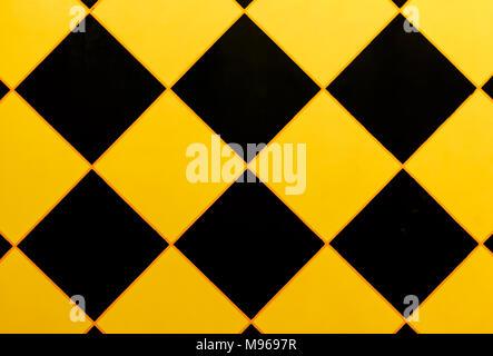 Modello della parete con un triangolo nero, diamante, nero e giallo. Foto Stock