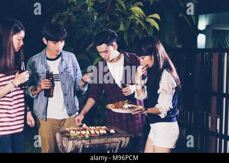 Gruppo asiatico di amici avente giardino barbecue a ridere con bevande birra bevande sulla notte Foto Stock