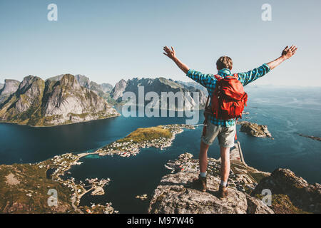 Uomo felice backpacker alzare le mani sulla cima della montagna lifestyle travel adventure outdoor vacanze estive tourist godendo di vista aerea in Norvegia Foto Stock