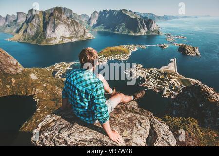 Uomo seduto sulla cima della montagna rupe sopra il mare e la roccia lifestyle travel adventure outdoor vacanze estive tourist godendo di vista aerea in Norvegia Lofot Foto Stock