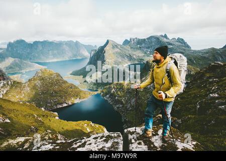 Uomo Barbuto traveler permanente sulla scogliera montagna in Norvegia viaggiare con lo zaino uno stile di vita sano adventure concept escursionismo attivo vacanze estive o Foto Stock