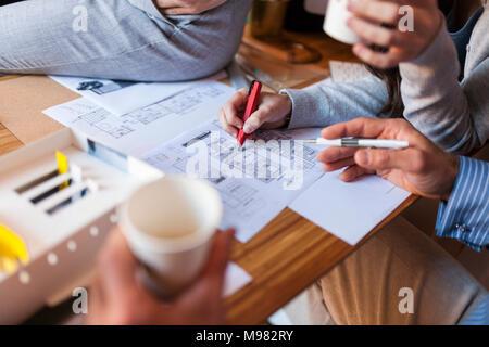 Team di architetti che lavorano su un progetto, discutendo il blueprint Foto Stock