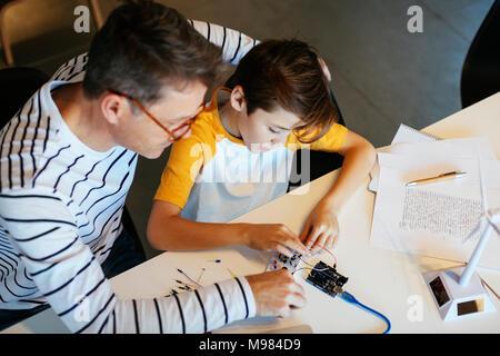 Padre e figlio il montaggio di un kit di costruzione con turbina a vento modello Foto Stock