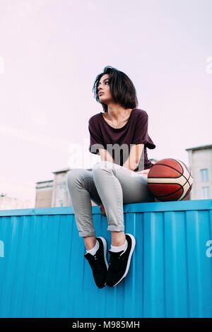 Giovane donna con basket seduta sul contenitore Foto Stock