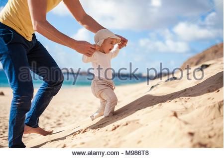 Spagna Lanzarote, baby ragazza camminare sulla spiaggia con l aiuto di suo padre Foto Stock