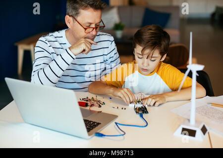 Padre e figlio il montaggio di un kit di costruzione con il computer portatile e la turbina eolica modello Foto Stock