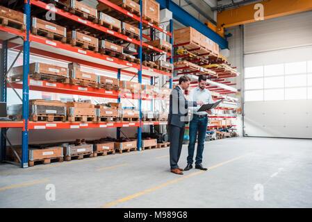 Due uomini camminare e parlare in fabbrica e negozio Foto Stock
