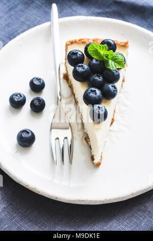 Cheesecake con mirtilli freschi sulla piastra bianca, il fuoco selettivo composizione verticale Foto Stock