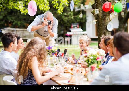 Festa di famiglia al di fuori nel cortile. Grande party in giardino. Nonno prendendo foto con una fotocamera.