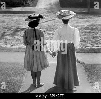 Due donne vittoriana il viso lontano e tenere le mani, ca. 1900. Foto Stock