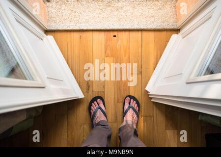 Buona mattina vacanze: Piedi di uomo di mezza età in flip-flop in piedi nella porta del balcone di un soleggiato rifugio per le vacanze Foto Stock
