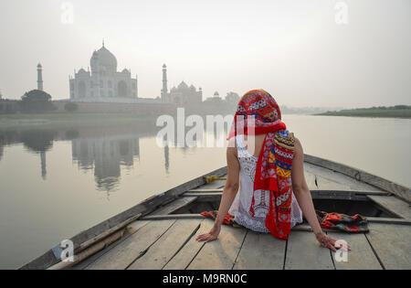 Una donna asiatica guardando il tramonto Taj Mahal da una imbarcazione in legno. Foto Stock