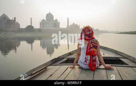 Una giovane donna guardando il tramonto Taj Mahal da una imbarcazione in legno. Foto Stock