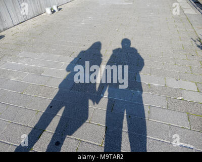 Ombre di un giovane uomo e donna tenendo le mani sulla strada. Foto Stock