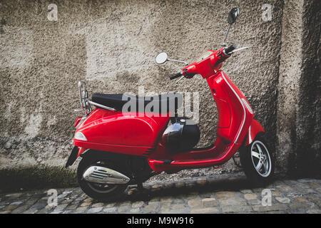Vintage scooter rosso parcheggiato di fronte a un muro grigio in Thun svizzera Foto Stock