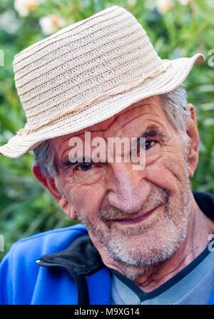 Un ritratto di un bel, sorridente uomo anziano in hat in piedi al di fuori. Foto Stock