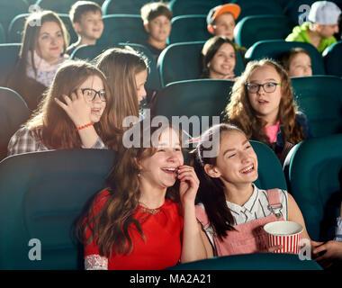 Felice ragazze ridendo e guardando i film interessanti nel cinema. Essi sorridente, guardando soddisfatto. Ci sono molti altri bambini emotivo sullo sfondo. Foto Stock