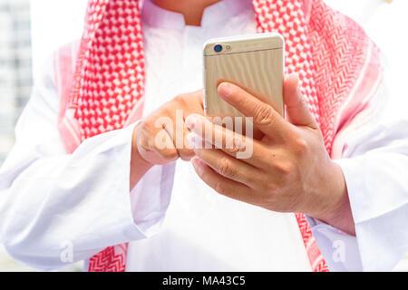 Arabia saudita Arab Emirates man mano texting in uno smart phone Foto Stock