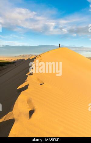 Uomo che cammina su Khongor dune di sabbia in Gobi Gurvan Saikhan Parco Nazionale. Sevrei distretto, a sud della provincia di Gobi, Mongolia. Foto Stock