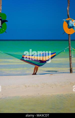 Donna rilassarsi in un'amaca sulla spiaggia di Holbox, Messico Foto Stock