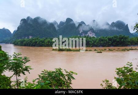Il Fiume Li e colline di pietra calcarea nella nebbia, Yangshuo, Guangxi, Cina Foto Stock