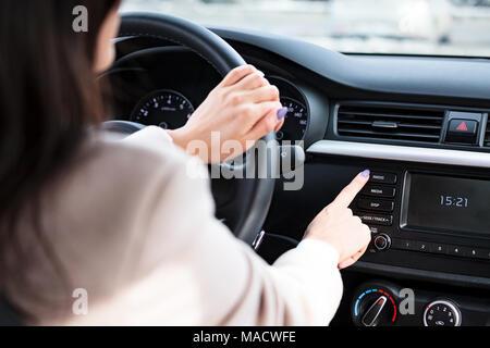 Donna premendo il pulsante radio su auto del pannello di