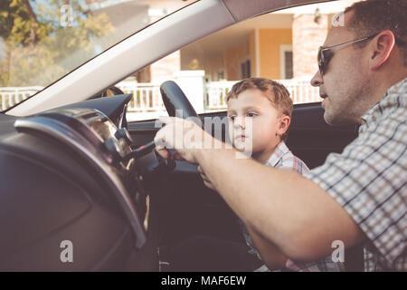 Felice il padre e il Figlio è seduto in macchina al giorno. La gente che ottiene pronto per il viaggio su strada. Concetto di famiglia felice.