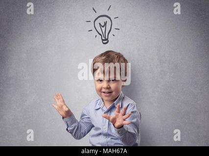 Smart little junior nella parte anteriore di un elaborato muro grigio con concetto infantili Foto Stock