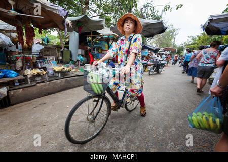 Donna di mezza età in bicicletta intorno al mercato Chhlong, Kratie Provincia, Cambogia del Sud-est asiatico Foto Stock