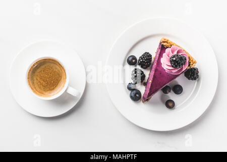 Vista superiore del pezzo di torta con frutti di bosco e la tazza di caffè isolato su bianco il piano portapaziente Foto Stock