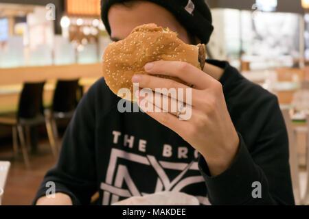 Giovane uomo mangiare hamburger Foto Stock