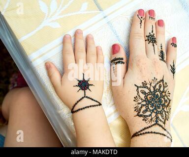 Le mani di una madre e un bambino con un tradizionale indiano fiore nero tattoes sul tavolo all'aperto close-up Foto Stock