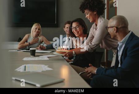 Un gruppo di uomini di affari che celebra una femmina di executive il compleanno nella sala conferenza. Team collega festeggia il compleanno in ufficio durante una meetin Foto Stock