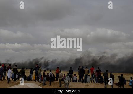 I dimostranti palestinesi guardare le nuvole di fumo si alzano dai pneumatici bruciati, per distrarre truppe israeliane, durante scontri lungo il confine tra Israele e la striscia di Gaza, a est di Khan Yunis, sud della striscia di Gaza, 03 aprile 2018. Foto: Mohammed Talatene/dpa Foto Stock