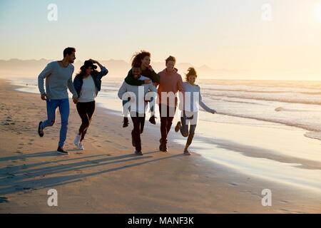 Gruppo di amici divertendosi in esecuzione lungo la spiaggia invernale insieme Foto Stock