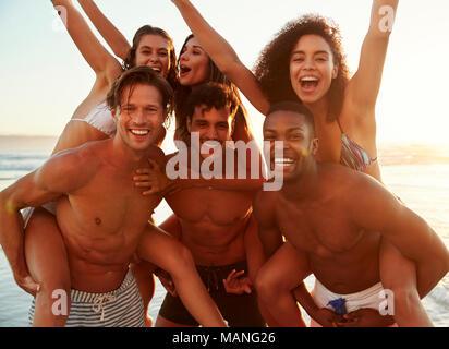 Gruppo di amici in vacanza avente Piggyback gara sulla spiaggia Foto Stock
