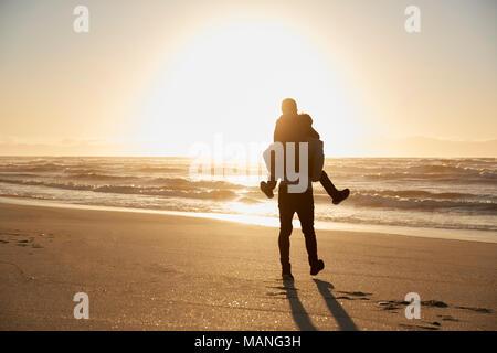 Silhouette di padre dando figlio piggyback sulla Spiaggia Invernale Foto Stock