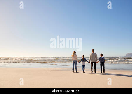 Vista posteriore della famiglia sulla spiaggia invernale tenendo le mani guardando il mare Foto Stock