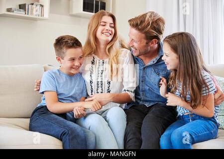 Famiglia sorridente rilassante sul divano di casa insieme Foto Stock